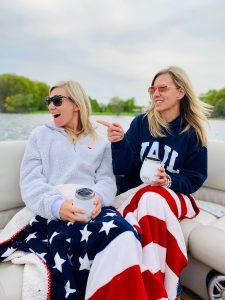 Amy and Jen on a boat with a cozy red, white, and blue blanket