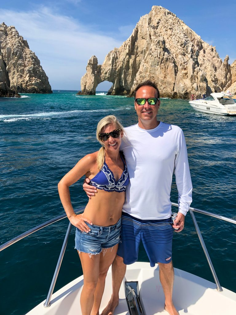 Barely B blogger standing on a boat with her husband in front of the arches in Cabo San Lucas