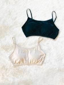 A nude color bra cover cami and a black bra cover cami .
