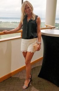 flat chested blonde woman in a black tank top, cream lace shorts, and snakeskin high heels