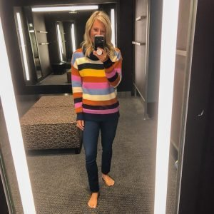 A petite flat chested blonde woman wearing a colorful striped sweater and dark jeans.