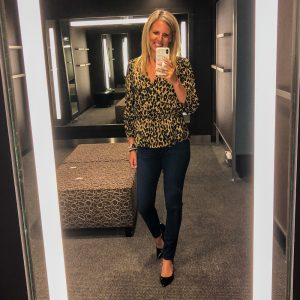 a flat chested blonde woman wearing a leopard print peplum top with denim jeans and black patient leather pumps.