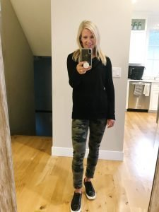 flat chested girl in a black turtleneck, Camo jeans, and black sneakers
