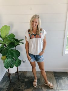 small busted blonde woman in a white top with colorful embroidery and jean shorts.