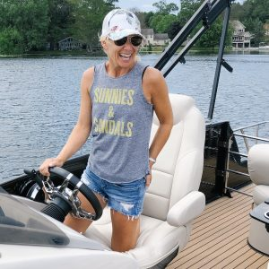 "flat chested woman driving a pontoon boat wearing a gray tank top that says ""Sunnies & Sandals"", jean shorts, and a floral baseball hat."
