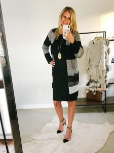 tall blonde wearing a black knee length dress with a black and grey cardigan and black pumps.