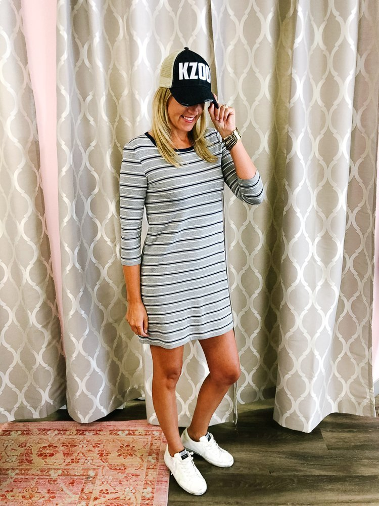 tall small chested blonde wearing a stripped cotton dress with a baseball cap and Golden Goose sneakers