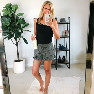 tall flat chested blonde wearing a black tank top and olive print shorts.
