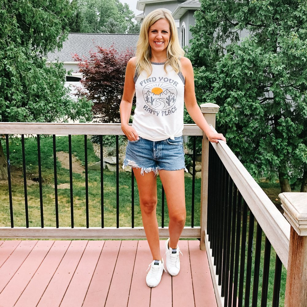 tall flat chested blonde woman wearing a graphic tee and cutoff jean shorts and sneaker standing on a deck.