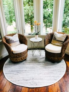 2 wicker swivel chairs on a round rug, small side table