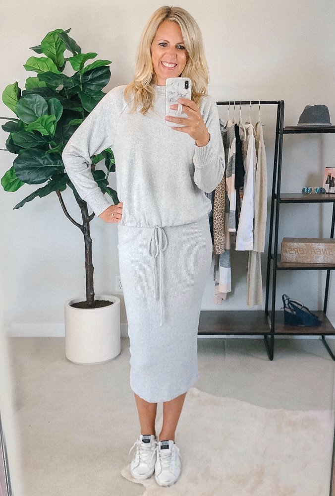 tall small chested blonde woman wearing a grey sweatshirt and matching mid-length skirt and golden goose sneakers