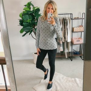 Tall blonde wearing a black legging and a pokadot top and black sneakers