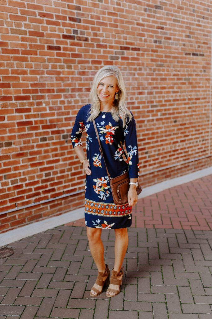 blonde woman in a navy blue floral dress