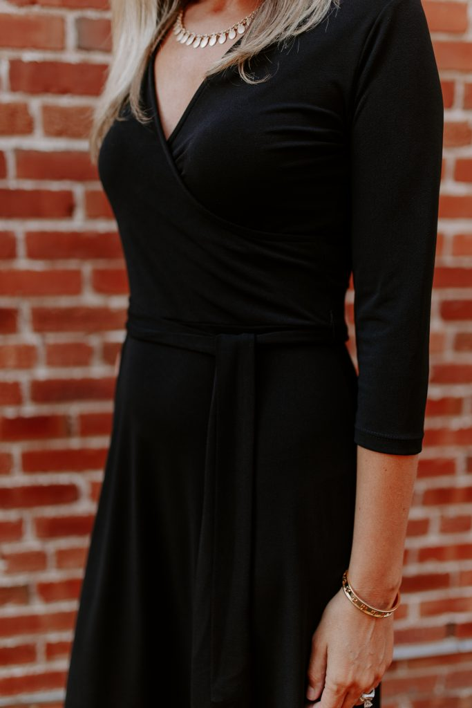 blonde woman in a black wrap dress