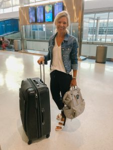 flat chested blonde woman in a jean jacket, white top, black pants and white Birkenstocks standing in an airport.