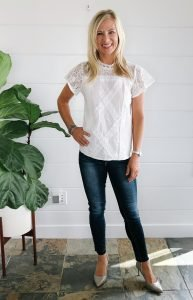 flat chested blonde woman in a white lace top with dark blue jeans