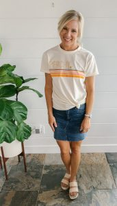 flat chested blonde woman in a graphic tee-shirt that says Peaches and a blue jean skirt