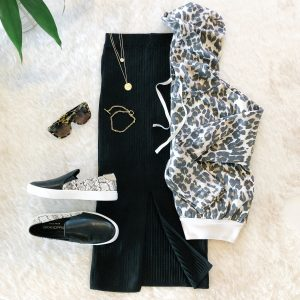 Flat lay with Free People black midi skirt and a cropped leopard print sweatshirt