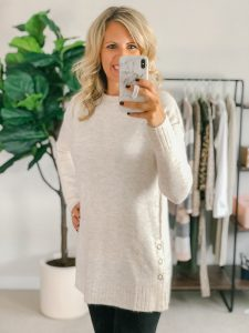 Blonde flat chested woman wearing a cream sweater with side snaps.