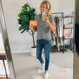 Tall Blonde wearing a grey leopard top, jeans and golden Goose sneakers