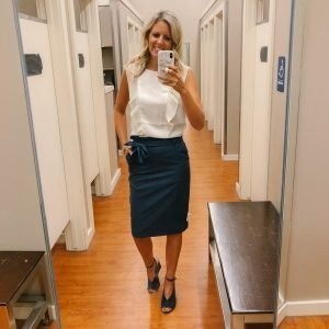 tall blonde wearing a cream blouse and a navy pencil skirt