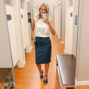 Tall blonde woman wearing a cream blouse and a navy blue tie pencil skirt and blue wedges