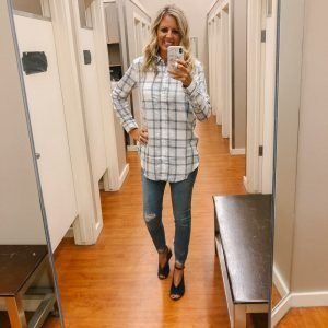 Tall blonde wearing a white plaid button up shirt and distressed raw hem light wash jeans.