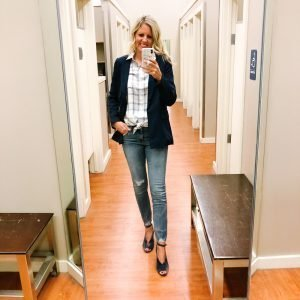 Tall blonde wearing a white plaid button up shirt and distressed raw hem light wash jeans with a boyfriend navy blazer.