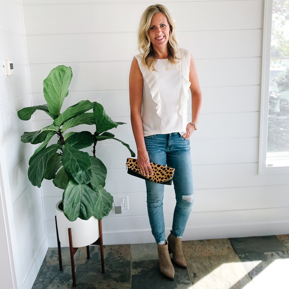 Tall blonde wearing a cream blouse and distressed raw hem light wash jeans with tan vince Camuto booties