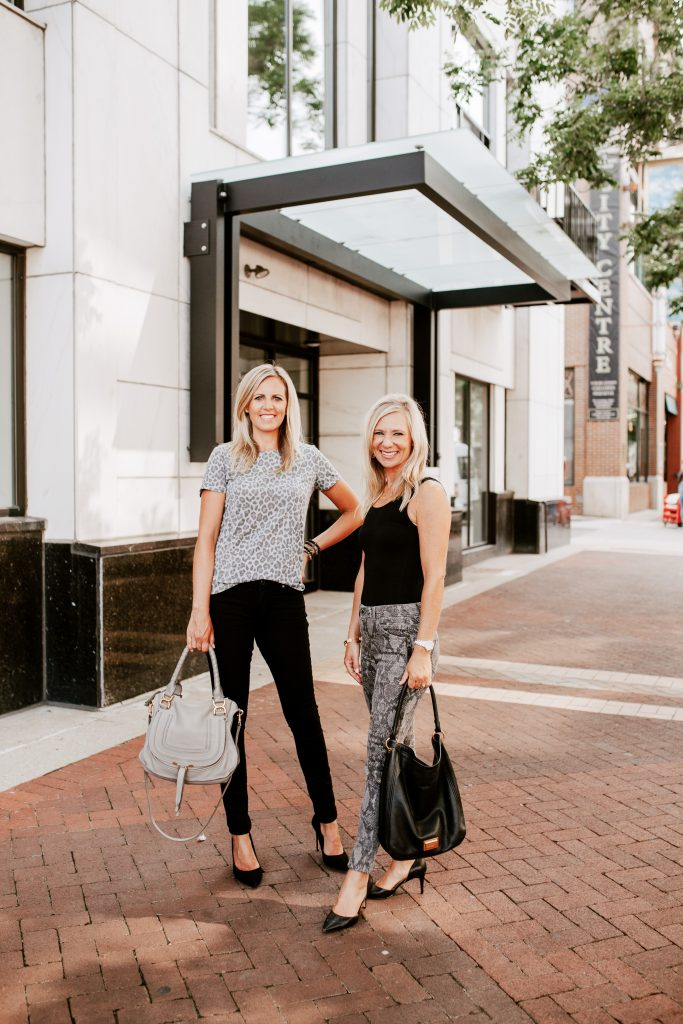 two blonde woman standing next to each other. The taller woman is wearing Target gray leopard print tee-shirt with raw hem black Hudson jeans and Steve Madden black heels carrying a gray Chloe purse. The shorter woman is wearing black Commando sleeveless bodysuit with gray snakeskin Wit to Wisdom jeans and carrying a Marc Jacobs black purse