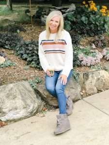 Blond woman wearing American Eagle Oversized Striped Crewneck Sweater, AG jeans, and Ugg Kriston Waterproof Bootie