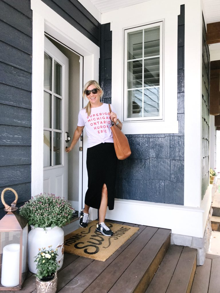blonde woman wearing Free Peoplel Skyline black midi skirt and J Crew Great Lakes graphic tee-shirt