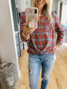 flat chested blonde woman wearing a Target red plaid shirt and distressed jeans