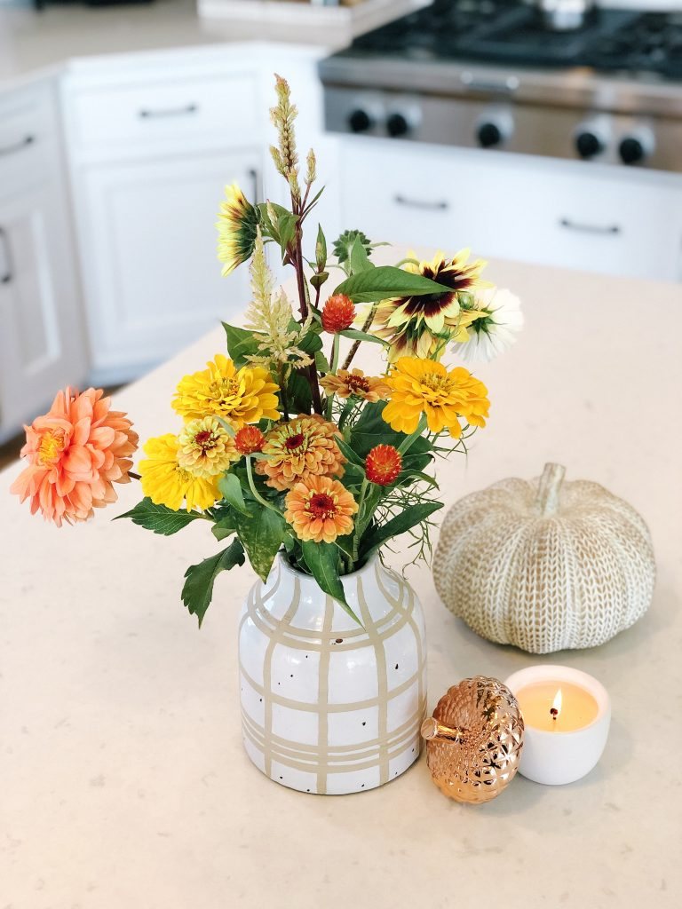 Fall flowers, pumpkin, and candle