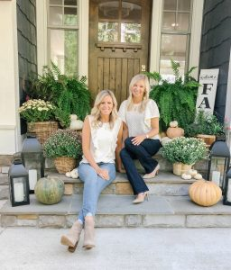 Two blonde women sitting on a fall front porch with creme tops and jeans