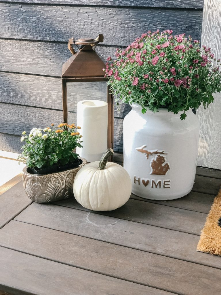 porch display with a copper planter, mums, and a white pumpkin
