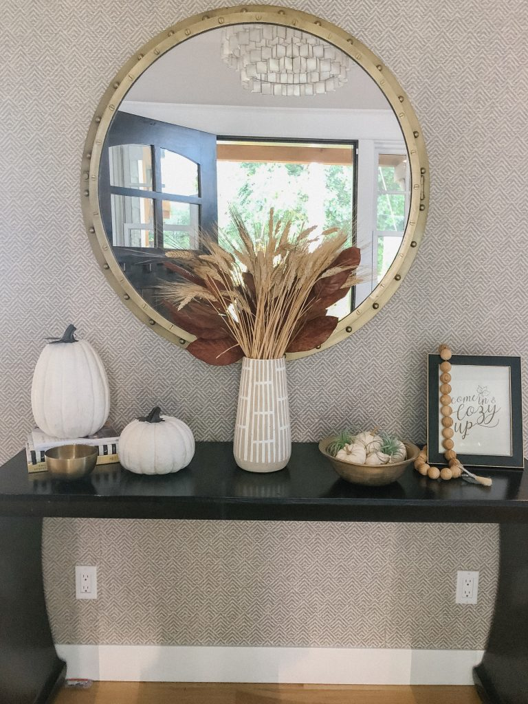 console table decorated for fall with white pumpkins and wheat grass