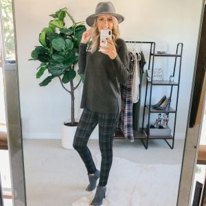 Tall blonde wearing plaid pants wiht a grey sweater and grey peep toe booties with a grey hat.