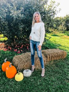 tall blonde standing in an apple orchard wearing a Fall cream sweater and AG Jeans with Vince Camuto tan booties