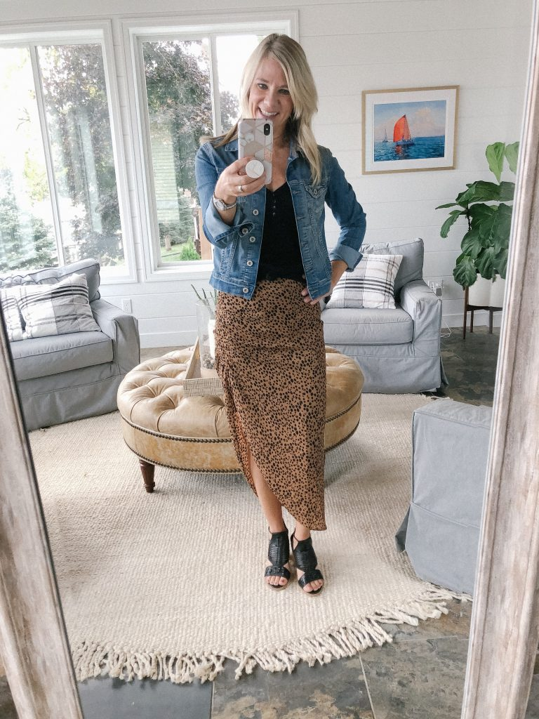 How to wear a midi skirt by The Barely B's, a lifestyle blog: image of woman standing inside her house wearing BB Dakota ruched awakening leopard midi skirt, a black tank top, a Blank NYC jean jacket and black open toe wedges.