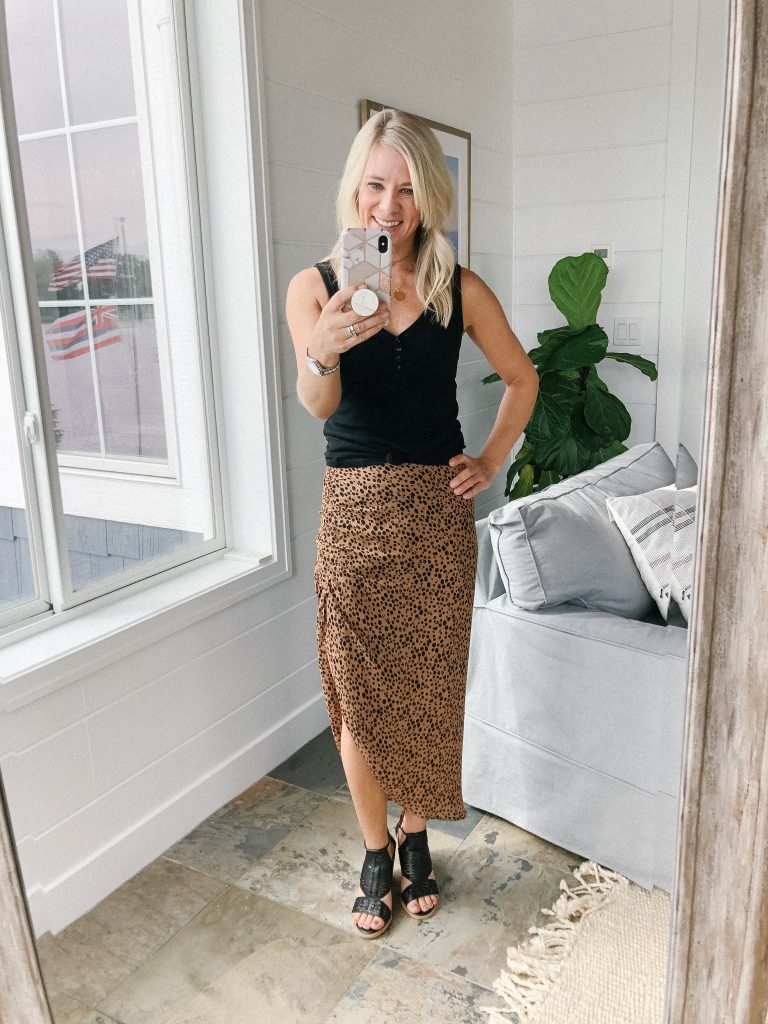 How to wear a midi skirt by The Barely B's, a lifestyle blog: image of woman standing inside her house wearing BB Dakota ruched awakening leopard midi skirt, a black tank top, and black open toe wedges.