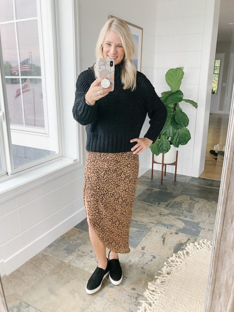 How to wear a midi skirt by The Barely B's, a lifestyle blog: image of woman standing inside her house wearing BB Dakota ruched awakening leopard midi skirt, a black Free People My Only Sunshine Cowl Neck Sweater, and black Caslon wedge sneakers.