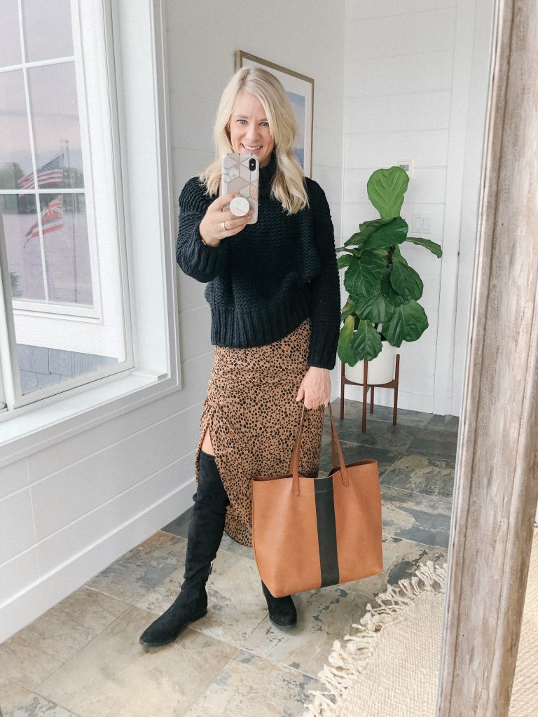 How to wear a midi skirt by The Barely B's, a lifestyle blog: image of woman standing inside her house wearing BB Dakota ruched awakening leopard midi skirt, Free People My Only Sunshine cowl neck sweater in neutral, Madewell messenger bag, and Steve Madden over the knee boots.