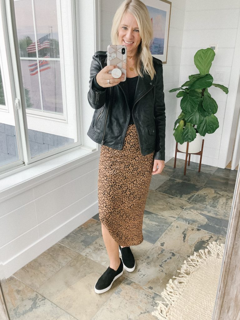 How to wear a midi skirt by The Barely B's, a lifestyle blog: image of woman standing inside her house wearing BB Dakota ruched awakening leopard midi skirt, a black tank top,a black Treasure & Blonde leather Moto jacket, and Caslon black wedge sneakers.