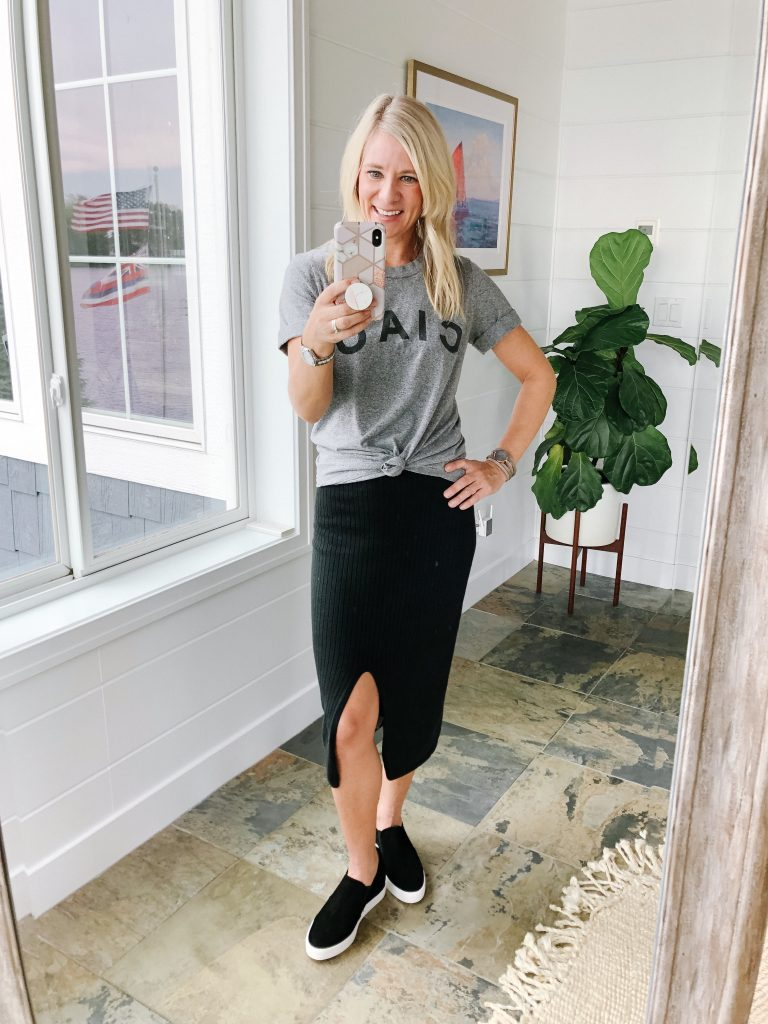 How to wear a midi skirt by The Barely B's, a lifestyle blog: image of woman standing inside her house wearing Free People Skyline Midi with a gray graphic tee-shirt that says Caio, and Caslon black wedge sneakers