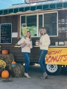 2 blondes standing in front of a food truck with Donuts and apple cider both wearing cream sweater, jeans and tan shoes