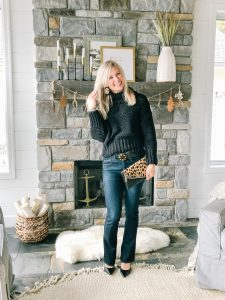 The Barely B's, a lifestyle blog: image of woman standing inside her house wearing Wit & Wisdom bootcut jeans, Free People My Only Sunshine cowl neck sweater in black, a leopard print clutch, and Sam Edelman black high heels