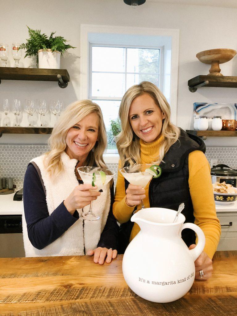 two blonde women toasting with jalapeño margaritas
