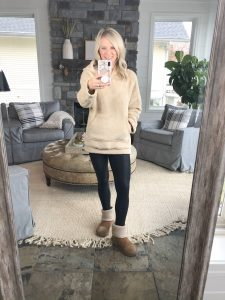Lifestyle blogger from the Barely B's standing in her home wearing a tan, fuzzy Amazon fleece, black leggings, and tan Ugg boots