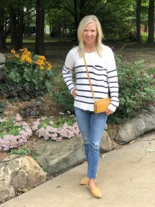 blonde woman standing outside wearing a Madewell cream and blue striped sweater and AG distressed denim and Steve Madden studded feather loafers in mustard.